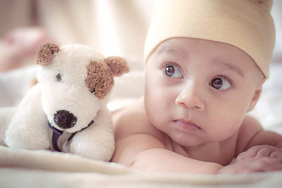 A baby and the plush toy next to it