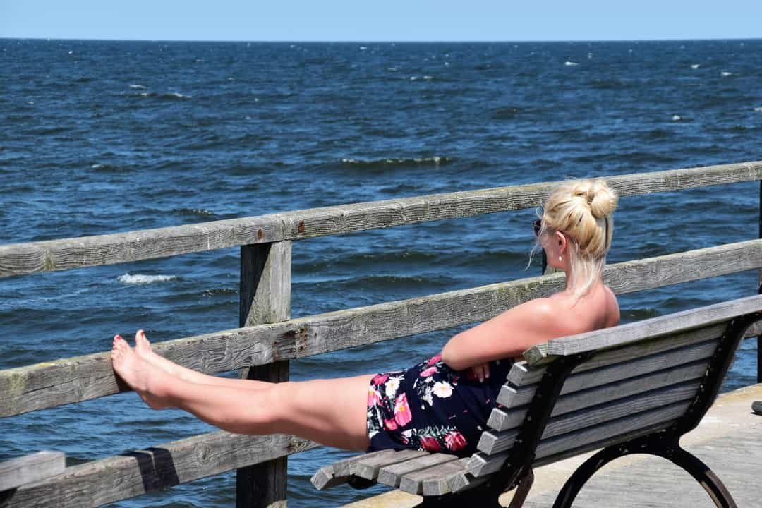 A woman sitting on a bench next to a body of water