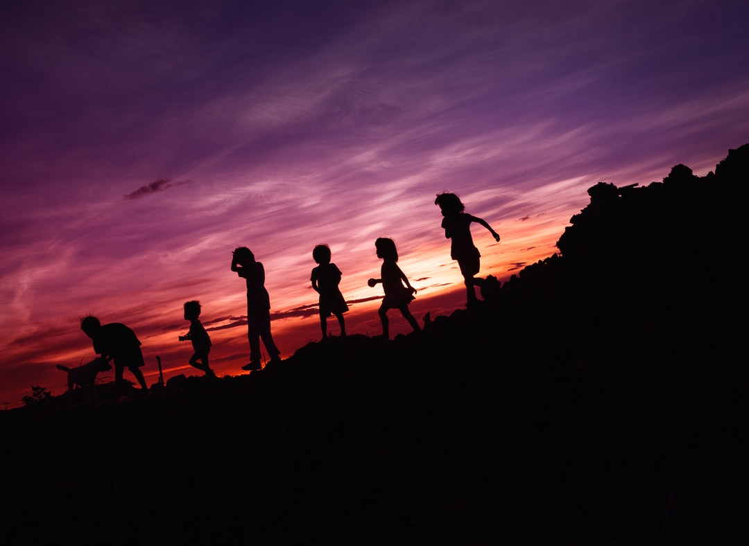 A group of people walking up a hill with a sunset in the background